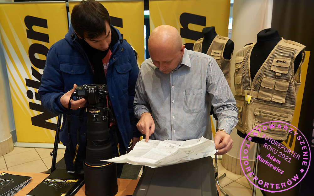 (L) Rafal Oleksiewicz (Pressfocus Agency) and (R) Wiktor Sobolewski (Nikon Poland) check new 400/2.8 by Nikon while Press Photo Expo Fair at Torwar Hall in Warsaw, Poland.<br /> Press Photo Expo is event for professional photographers. There are photo exhibitors, workshops, presentations and seminars.<br /> <br /> Warsaw, Poland, January 12, 2015<br /> <br /> Picture also available in RAW (NEF) or TIFF format on special request.<br /> <br /> For editorial use only. Any commercial or promotional use requires permission.<br /> <br /> Mandatory credit:<br /> Photo by &copy; Press Photo Expo