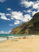 People enjoying the surf at Polihale State Park and its barking sands on the west coast of Kauai, Hawai'i.