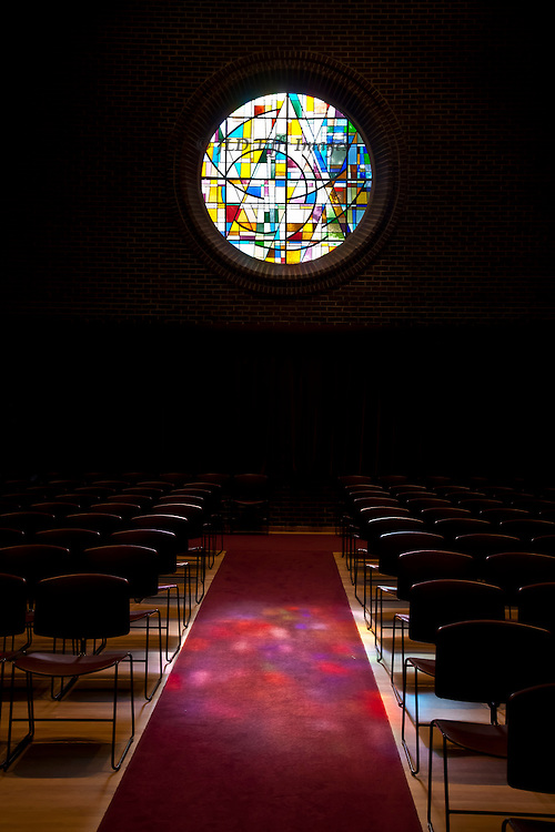 Circular stained glass window in an abstract geometrical design casts its colored lights on the church aisle.  Rows of empty chairs on each side just visible in the dark, as the window provides the only illumination here.