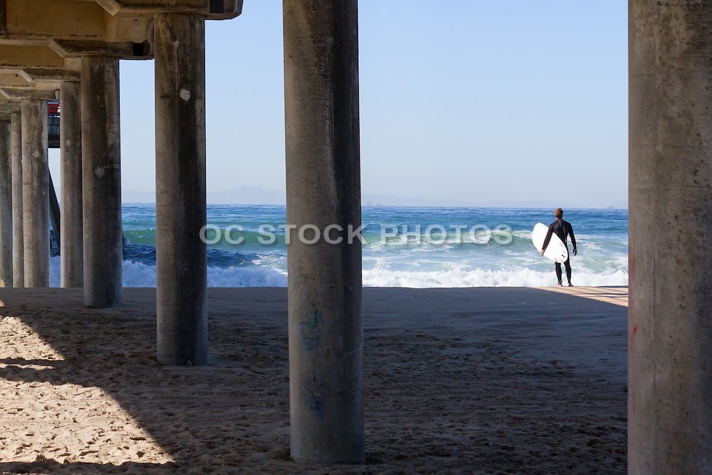 Man with Surfboard Watching Waves Come in at Huntington Beach Pier, California