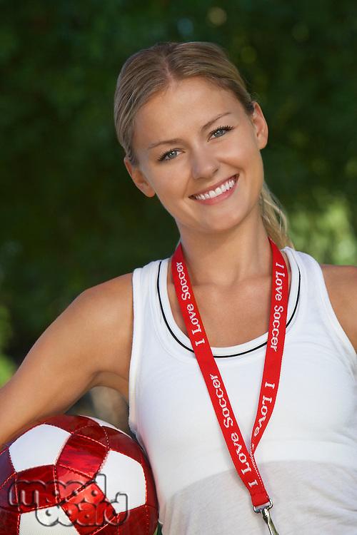 Female coach holding soccer ball under arm, portrait