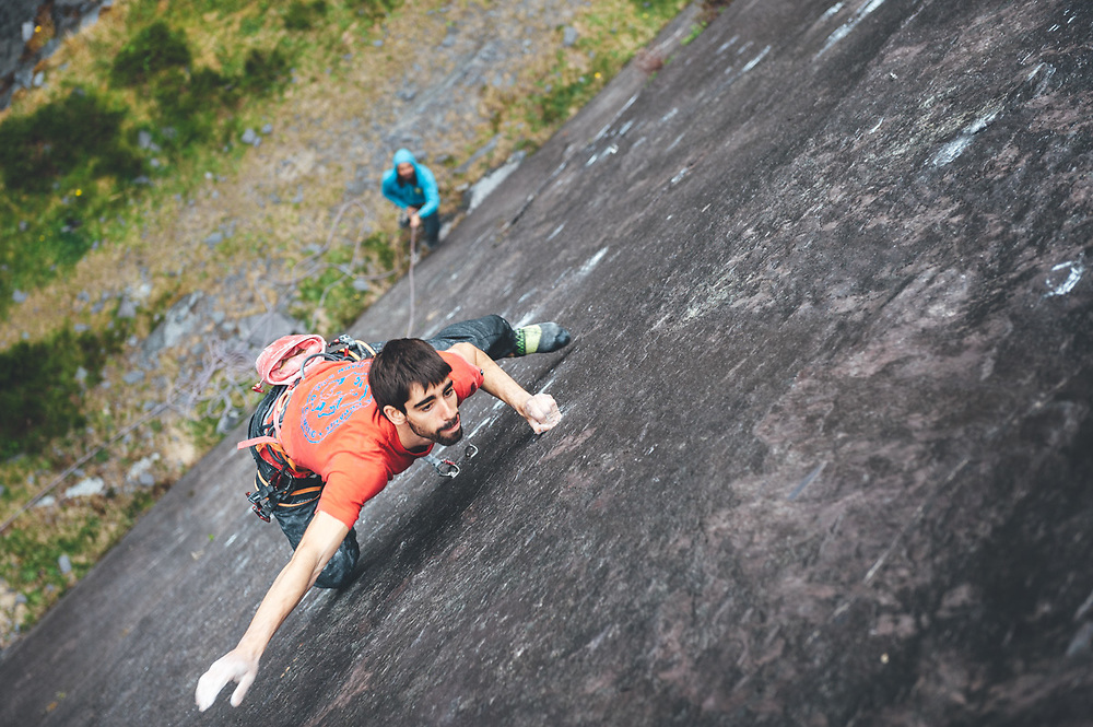 Climber climbing at stuning walls of the ancient Dinorwic Quarry at Snowdonia National Park in North Wales.