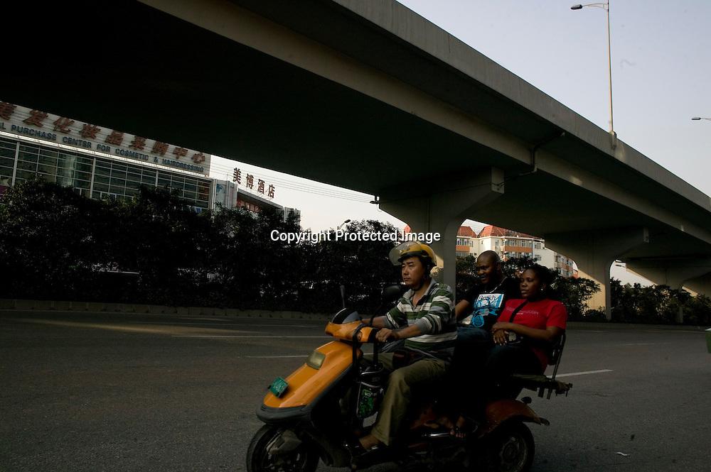 GUANGZHOU, 3. Mai , 2010:.ein Chinesicher Tuk-Tuk Fahrer mit 2Afrikanern auf einer Strasse in Guangzhou...