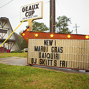 "Sign in front of the Geaux Cup, a bar near Eunice, Louisiana catering to Mardi Gras celebrants. The Courier de Mardi Gras in Eunice is a 15-mile music and dance filled 'run' through the rural bayou-land with costumed revelers play-acting at begging (rooted in the fête de la quémande (""feast of begging"") of Medieval France) and chasing chickens in order to collect the ingredients for the communal gumbo. The event is celebrated in Cajun communities in Louisiana on final day before Lent."