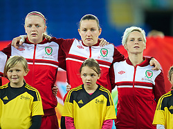 CARDIFF, WALES - Thursday, September 26, 2013: Wales' Helen Bleazard, goalkeeper Nicola Davies and captain Jessica Fishlock sing the national anthem as they line-up before the FIFA Women's World Cup Canada 2015 Qualifying Group 6 match against Belarus at the Cardiff City Stadium. (Pic by David Rawcliffe/Propaganda)