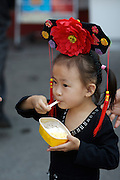 Gugong (Forbidden City, Imperial Palace). Little girl dressed as princess having ice cream.