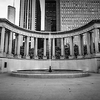 Chicago Millennium Monument in black and white.  Located in Wrigley Square in Millennium Park, the peristyle monument and fountain has greek style columns and contains the names of the founders of Millenium Park.