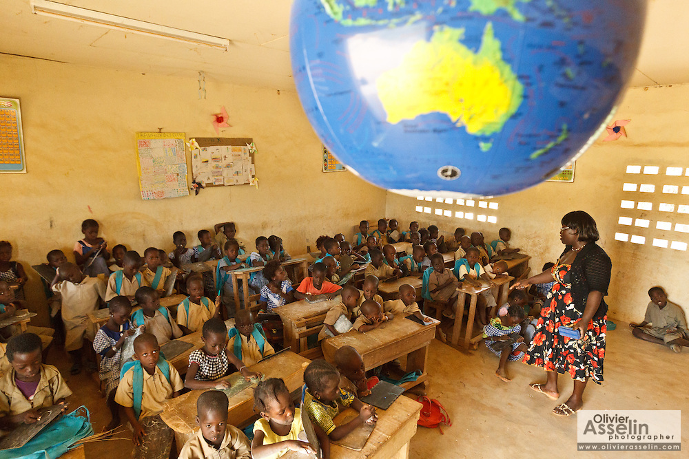 An inflatable terrestrial globe hangs from the ceiling as children attend class at the Faye primary school in the town of Faye, Bas-Sassandra region, Cote d'Ivoire on Monday March 5, 2012. The class has 79 students, and the school has been forced to refuse any additional students.