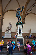 Tourists sit beneath the scultpure by Benvenuto Cellini of Perseus with the Head of Medusa, Loggia dei Lanzi, Piazza della Signoria, Florence, Italy