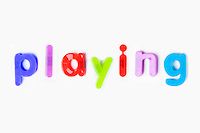 Colorful alphabet magnets spelling 'playing' over white background