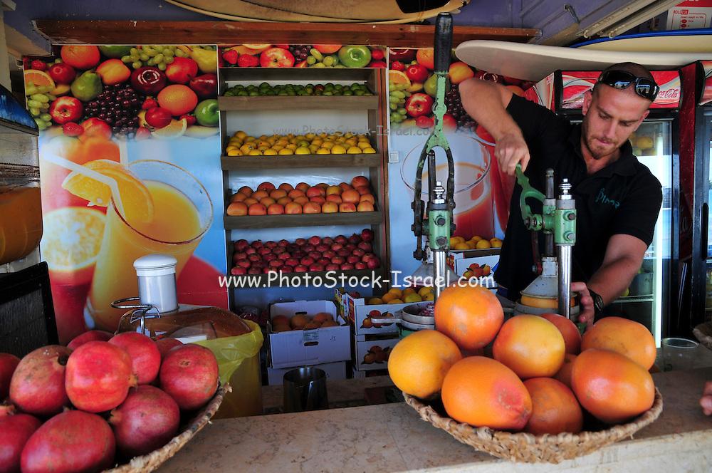 Israel, Haifa, a fruit juice kiosk man squeezes oranges