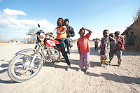 07 OCT 2009, MOSHI/TANZANIA:<br /> Frau auf einem Motorrad mit einem Mann auf dem Sozius und neugierigen Kindern eines Dorfes, das durch ein von der KfW finanziertes Projekt eine Trinkwasserversorgung durch einen Hochtank erhalten hat, ONE Informationsreise nach Tansania, Moshi / Kilimandscharo<br /> IMAGE: 20091007-01-286<br /> KEYWORDS: Reise, Trip, Kind, Kinder