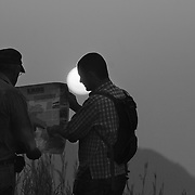 Nol (L) and Digby look at a map at an observation post in Phou Hin Poun national park, Laos.