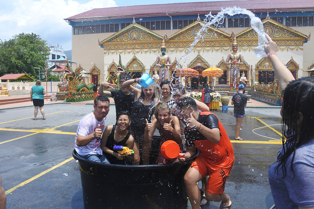 People at the Songkran festival throwing water in buckets at each other from a alrge tank of water, water is frozen in motion