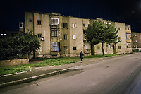 TARANTO, ITALY - 22 FEBRUARY 2018: A woman walks her dog by a residential building in Tamburi, the working-class district adjacent the ILVA steel mill in Taranto, Italy, on February 22nd 2018.<br /> <br /> Taranto, a  formerly lovely town on the Ionian Sea has for the last several decades been dominated by the ILVA steel mill, the largest steel plant in Europe. It was built by the government in the 1960s as a means of delivering jobs to the economically depressed south, but has been implicated for a cancer as dioxin and mercury have seeped into local groundwater, tainting the food supply, while poisoning the bay and its once-lucrative mussels.