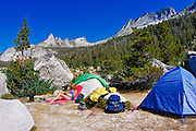 Woman relaxing in camp under Echo Peaks and Matthes Crest (backpacking gear visible), Yosemite National Park, California