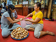 31 MAY 2017 - CHACHOENGSAO, THAILAND:  Women with offerings of hard boiled eggs at Wat Sothon (also spelled Sothorn) in Chachoengsao, Thailand. The temple is one of the largest and most visited in Thailand. People make merit by paying to wrap the Buddha statues in orange robes. The temple is most famous because people leave hard boiled eggs as an offering at the temple. They ask for business success or children and leave hundreds of hard boiled eggs.     PHOTO BY JACK KURTZ