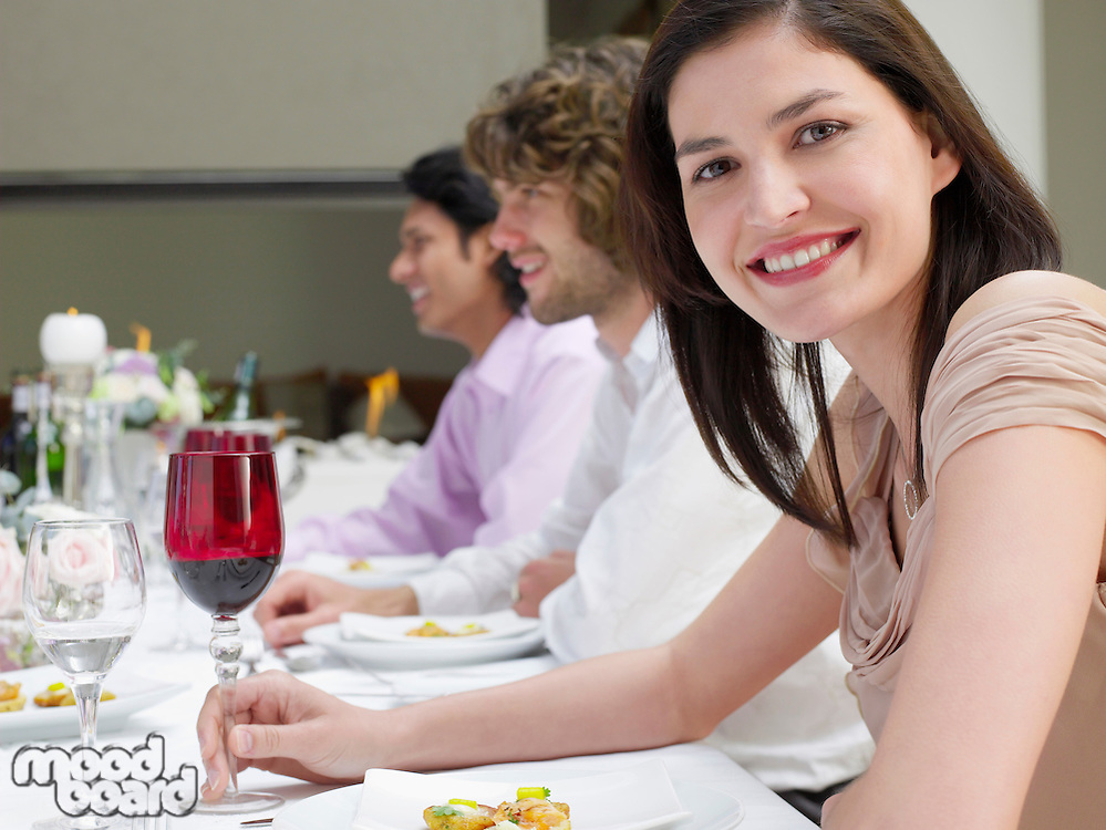 Young woman in dress sitting at table of formal dinner party side view