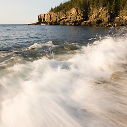 Waves wash over the cobblestones of Monument Cove Maine USA