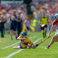 Clare's Podge Collins tries to keep the ball in play while challanged by Cork's Sean O'Donoghue