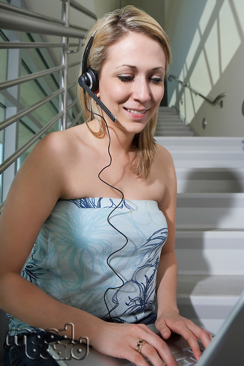Female student using laptop with headset on stairs