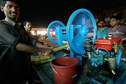 BANGLADESH DHAKA KAWRAN BAZAAR 1MARB05 - A trader pushes sugarcane though his press powered by a small diesel engine at Kawran Bazaar vegetable market. The Bazaar has been in the Tejgaon area for at least 30 years and is one of the largest markets in Dhaka city...jre/Photo by Jiri Rezac ..© Jiri Rezac 2005..Contact: +44 (0) 7050 110 417.Mobile:  +44 (0) 7801 337 683.Office:  +44 (0) 20 8968 9635..Email:   jiri@jirirezac.com.Web:    www.jirirezac.com..© All images Jiri Rezac 2005- All rights reserved.