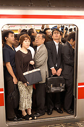 Very crowded carriage on Tokyo subway during rush hour