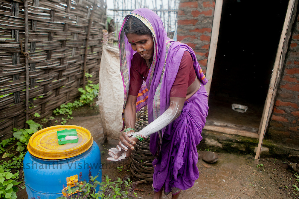 Sorekasa, Jivati Block, Dist. Chandrapur. .55 year old Bhimbai Atram  washes her hand outside her toilet constructed under Nirmal Bharat Abhiyan  as a part of Bio Village project.  Bio Village is a part of the over all obejective of the Water Hygiene and Sanitation project ( WASH). UNICEF partners with the State nodal Department, Water Supply and Sanitation Department under the State Government and District level TSC, Divisions, Key resource Centres and NGOs. Special initiatives have been undertaken in the State such as Bio-Village Project in IDPs, WASH Compliance in Schools, Multiple Use Water Services project (MWUS), Sanitary Napkin production and promotion of menstrual hygiene, Risk based rapid assessment of water quality as per JMP manual and NGP concurrent monitoring.UNICEF India/2012/Vishwanathan