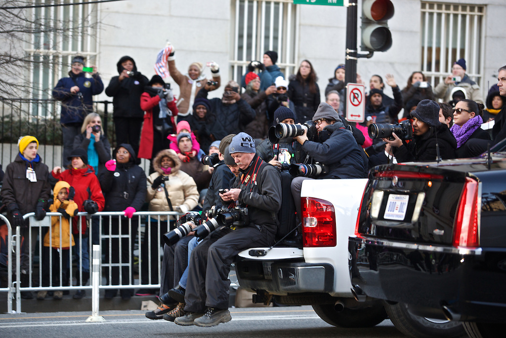 Members of the media travel on trucks in front of the presidential motorcade during the inauguration parade on January 21, 2013 in Washington, D.C.