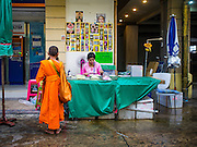 25 AUGUST 2016 - BANGKOK, THAILAND: A novice monk on his morning alms rounds solicits a donation from a vendor in the flower market in Bangkok. Most Thai males enter the monastery and become monks or novices (young monks) at some point in their lives.         PHOTO BY JACK KURTZ