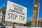 "No TTIP European Day of Action – as part of a day of protest across the EU.  The Transatlantic Trade and Investment Partnership (TTIP) is supposed to be 'free trade' deal and is currently being negotiated by the EU and US. Protestors are concerned that the ""deal will give big business more power over society, the environment, public services and democracy"". Parliament Square, London 11 Oct 2014."