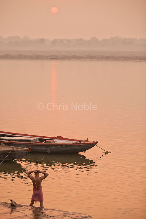 A man performs his morning puja (respect) ceremony by ritually bathing in the Ganges River, Varanasi India.