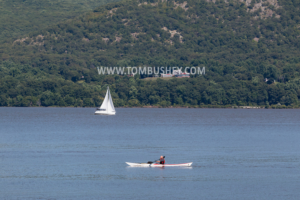 New Windsor, New York - A man in a kayak paddles north while a sailboat heads south on the Hudson River scenes in a view from Plum Point on July 31, 2015.
