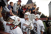 SHOT 5/11/13 7:47:40 PM - Denver's Carson Cannon #26 high fives fans with teammates after beating the University at Albany in their first round NCAA Tournament lacrosse game at the Peter Barton Lacrosse Stadium on the University of Denver campus Saturday May 11, 2013. The University of Denver won the game 19-14 to advance. (Photo by Marc Piscotty / © 2013)