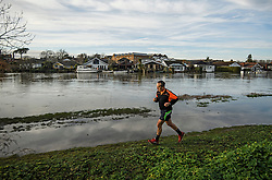 © Licensed to London News Pictures. 22/12/2019. Thames Ditton, UK. A man jogging along the bank of The River Thames which has burst it's banks at Thames Ditton, Surrey. Further weather warnings are in place following flooding and high winds in parts of the UK . Photo credit: Ben Cawthra/LNP