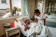 Nurse Almaz Deressa talks to a patient who came to the Hamlin Fistula Hospital in Addis Ababa, Ethiopia from Somalia. The patient, 20 years old, was in labor for three days before she gave birth to a stillborn baby and suffers from vaginal fistula and dropfoot. After only 24 days, she came to Hamlin Fistula Hospital for treatment. (photo by Mary F. Calvert)