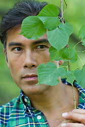 Asian American man looking out from behind a vine plant