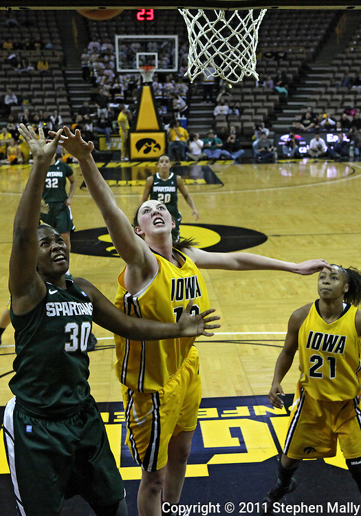 January 27 2010: Michigan St. forward Lykendra Johnson (30) and Iowa center Morgan Johnson (12) battle for a rebound as Iowa guard Kachine Alexander (21) looks on during the first half of an NCAA women's college basketball game at Carver-Hawkeye Arena in Iowa City, Iowa on January 27, 2010. Iowa defeated Michigan State 66-64.