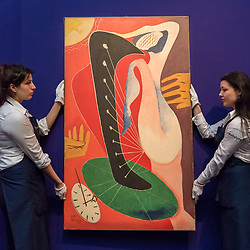 "© Licensed to London News Pictures. 20/02/2019. LONDON, UK. Technicians hold ""Femmelaharpe"", 1957, by Man Ray, (Est. £0.7-1.0m). Preview of Sotheby's Impressionist & Modern and Surrealist Art sales.  The auction will take place at Sotheby's New Bond Street on 26 February 2019.  Photo credit: Stephen Chung/LNP"