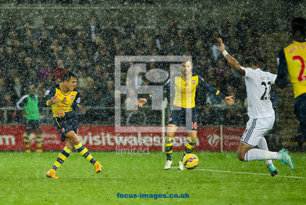 Alexis S&aacute;nchez (left) of Arsenal scores his sides first goal during the Barclays Premier League match at the Liberty Stadium, Swansea<br /> Picture by Tom Smith/Focus Images Ltd 07545141164<br /> 09/11/2014