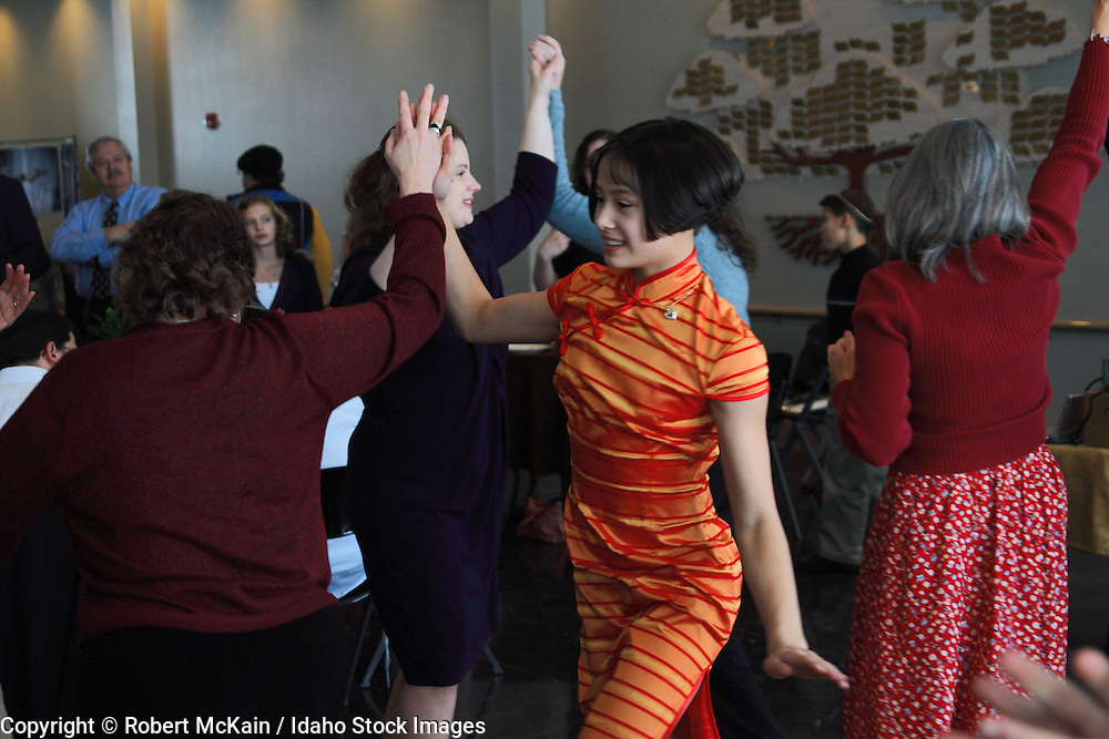 IDAHO. Boise. Asian Jewish girl dancing the Chabadic Womens Dance with friends at her Bat Mitzvah. December 2008. #pa080734 MR