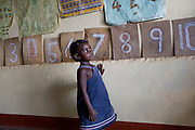A young girl learns to count using numbers on the wall at Miles2Smiles Welfare Centre in Kalerwe market, Kampala, Uganda. The centre is a day care and welfare service for market vendors with babies and infants aged 6 months to 5 years old.