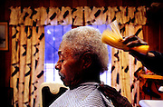 "(01/05/05) Bluff Road Diaries - ""I'm going to do this till I can't stand up,"" said Odell Jackon as he finished cutting Bill Dixon's hair at Jackson's barber shop on Bluff Road. Dixon, 76, has been getting his haircut from Jackson since 1973. ""I don't know what makes him a good barber but I've always been satisfied."" . ""Just  being here is unique,"" said owner Odell Jackson, 58. ""You should see all the different people that you meet."".The old building used to be a seamstress shop and a Magistrate's office. ""Then I dropped in."""