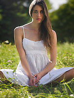 Portrait of young woman sitting cross-legged in meadow