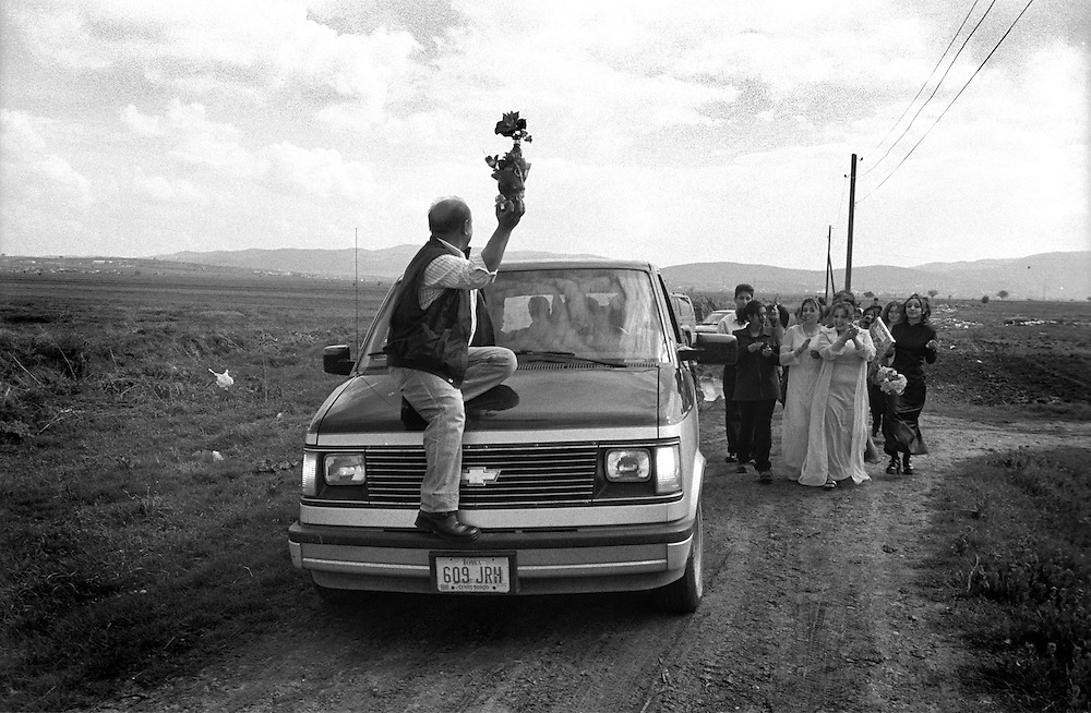Engagement party in a Kosovo roma family - The family of the groom are on their way to the brides home. The two families will then eat and drink while they dramatically discuss and fight over the amount of money the groom?s family will pay. The car was provided by an American activist, the man on the front is the groom?s father, carrying a bottle of alcohol that the families will share when the price has been fixed. ..Lapje Selo enclave, Kosovo.