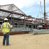 A rigger with Advanced Building Concepts from Tuscaloosa, Alabama, guides a steel truss as its lifted by crane to go into place on the new student services building under construction at the Tupelo Campus on Tuesday afternoon.