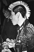 Male Punk with a mohican, and a girl, Drinking pints, UK, 1980's.