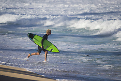 December 16, 2017 - Banzai Pipeline, HI, USA - BANZAI PIPELINE, HI - DECEMBER 16, 2017 - John John Florence of Hawaii runs into the surf at Off The Wall for a free surfing session before the start of the Billabong Pipe Masters Saturday. (Credit Image: © Erich Schlegel via ZUMA Wire)