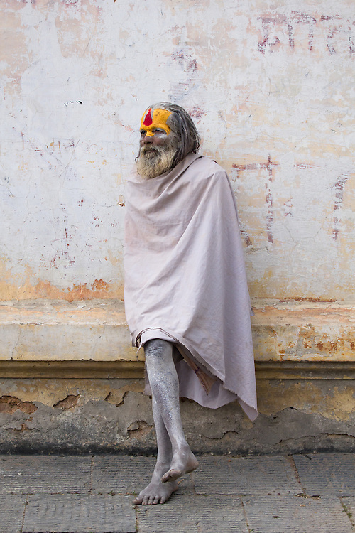 A hindu sadhu (holy man) with a white blanket, sitting on a ledge at the temple complex of Pashupatinath, near Kathmandu, Nepal.