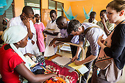 Dr Godfrey Kambanga, Dr Peter O'Reilly and Dr Siobhan Neville examine a patient on the children's ward during the daily rounds.  The rounds are attended by all the medical staff who work on that ward, doctors, nurses and attendants. St Walburg's Hospital, Nyangao. Lindi Region, Tanzania.